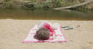 Young girl sunbathing on a river beach wearing colorful swim wear stock video