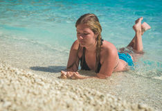 Young girl sunbathing in sea water splashing around her Royalty Free Stock Photo