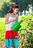 Young Girl in Sundress Watering Plants Stock Images