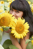 Young girl with sunflowers in field Stock Photo