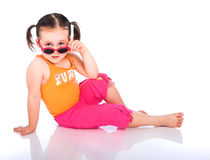 Young Girl with Sunglasses. Young girl in pigtails sitting down with sunglasses Stock Image