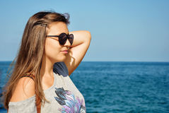 Young girl with sunglasses. Pretty young girl with sunglasses on at the beach Royalty Free Stock Photography