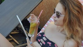 Young lady in bikini drinks cocktail and uses tablet stock video footage