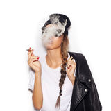 Young girl in sunglasses and black leather jacket smoking cigar Royalty Free Stock Photos
