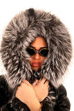 The young girl in sunglasses and a fur hood Royalty Free Stock Image