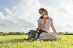 Young girl in sunglasses and hat drinks summer berry drink with ice sitting on green grass, copy space, golden hour royalty free stock image