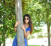 Young girl  with sunglasses hugging a tree Royalty Free Stock Photography