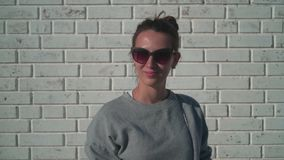 A young girl in sunglasses is looking into the camera and smiling against a white brick wall. Cute young girl smiling. A young girl in sunglasses is looking stock footage