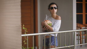 Young girl in sunglasses in the morning standing with the coconut and drinking its juice through the straws. Stylish. Young girl in sunglasses in the morning is stock video footage