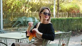 Young girl in sunglasses sitting chair in cafe. Autumn season time stock video