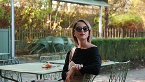 Young girl in sunglasses sitting chair in cafe. Autumn season time stock video footage