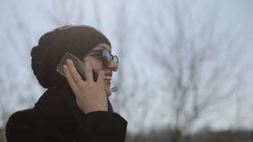 Young girl in sunglasses speaks by phone. Close up stock footage