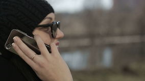 Young girl in sunglasses speaks by phone. Close up stock video footage