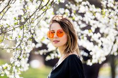Young girl in a sunglasses stay near a flowering tree stock images