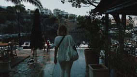Young girl with sunglasses walking on city street on vacations. Travel and tourism in beautiful places on Crete, Greece. stock footage