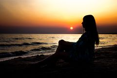Young girl at sunset in summer near the sea sits on the sand looking into the distance. silhouette at sunset. Silhouette of a young girl sitting on the sand royalty free stock images