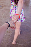 Young girl supporting man, holding hand on the beach Royalty Free Stock Photo