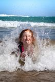 Young girl in surf at Makorori Beach, near Gisborne, New Zealand. Nine year old red haired girl in surf,at Makorori Beach, Gisborne, New Zealand, on a clear stock image