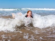 Young girl in surf at Makorori Beach, near Gisborne, New Zealand. Nine year old red haired girl in surf,at Makorori Beach, Gisborne, New Zealand, on a clear stock photo