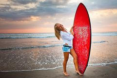 Young girl with surfboard at the beach Stock Photos