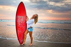 Young girl with surfboard at the beach Stock Photography