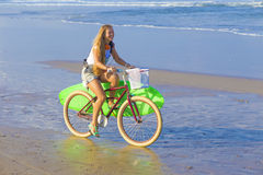Young girl with surfboard and bicycle Royalty Free Stock Photography