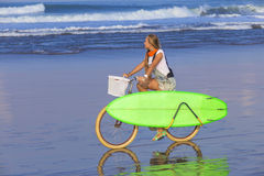 Young girl with surfboard and bicycle Stock Image