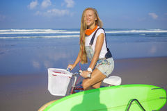 Young girl with surfboard and bicycle Royalty Free Stock Photos
