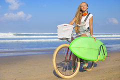 Young girl with surfboard and bicycle Royalty Free Stock Images