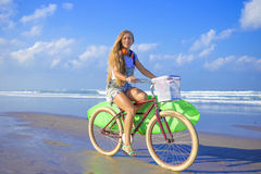 Young girl with surfboard and bicycle Royalty Free Stock Photo