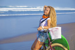 Young girl with surfboard and bicycle Stock Images