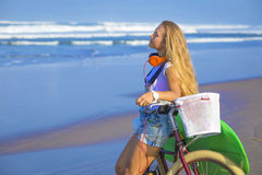 Young girl with surfboard and bicycle Stock Photos