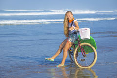 Young girl with surfboard and bicycle Royalty Free Stock Image