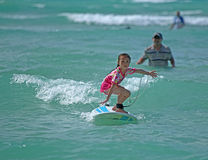 Young girl surfing. Young girl learning to surf Royalty Free Stock Image
