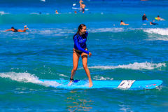 Young girl surfing standing up in Waikiki Beach Hawaii Stock Photography