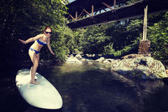 Young girl surfing the wave of the river on a surfboard Stock Images
