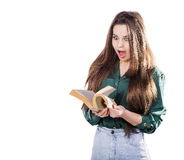 Young girl surprised, flipping through the pages of the book to. Isolate. Is reading. Shock Stock Photos