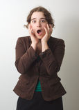Young girl surprised or horrified on gray background Stock Image