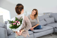 Young girl surprising her mother with flowers Royalty Free Stock Image