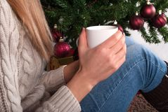 Young Girl in sweater holding cup of coffee in hand at legs with warmers and Christmas tree in the background. Young female legs with warmers on floor carpet Stock Images