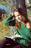 Young girl in sweater sitting under tree reading Royalty Free Stock Image