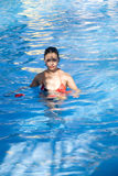 Young girl in swiming pool. Blue water red flowers floating Stock Images