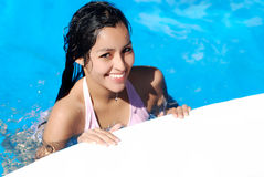 Young girl in swiming pool. Girl coming out of water by side of pool Royalty Free Stock Photo