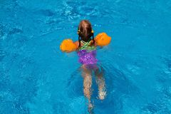 Young girl swiming in the pool. holiday idyllic.. Young girl swiming in the pool. Clear water and hot sunny day. Summer background for traveling and vacation Royalty Free Stock Photos