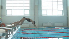Young girl swimmer, that jumping and diving into indoor sport swimming pool. stock footage
