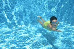 Young girl swimmer swimming under water in pool and has fun, teenager diving underwater, family vacation, sport and fitness Stock Images