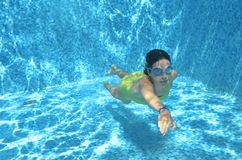 Young girl swimmer swimming under water in pool and has fun, teenager diving underwater, family vacation, sport and fitness Royalty Free Stock Photography