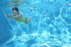 Young girl swimmer swimming under water in pool and has fun, teenager diving underwater, family vacation, sport and fitness Royalty Free Stock Images