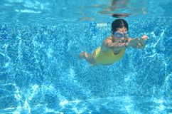 Young girl swimmer swimming under water in pool and has fun, teenager diving underwater, family vacation, sport and fitness Stock Image