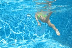 Young girl swimmer swimming under water in pool and has fun, teenager diving underwater, family vacation, sport and fitness Stock Photo